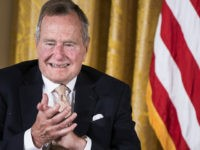 Former US President George H. W. Bush applauds during an event in the East Room of the White House July 15, 2013 in Washington, DC. US President Barack Obama hosted former US President George H. W. Bush and Barbara Bush to honor the 5000th Daily Point of Light Award which is a program started in response to Bush's call for volunteerism. AFP PHOTO/Brendan SMIALOWSKI        (Photo credit should read BRENDAN SMIALOWSKI/AFP/Getty Images)