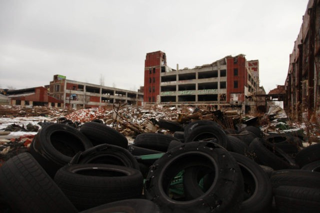 DETROIT, MI- DECEMBER 13: Old tires rest near the abandoned Packard Automotive Plant December 13, 2013 in Detroit, Michigan. Peru-based developer Fernando Palazuelo made his final payment on the Packard Plant, which he won during a Wayne County auction for $405,000. Palazuelo plans on developing the former automotive plant where …
