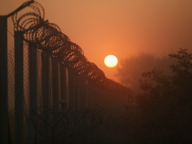 The sun rises over the nearly completed border fence at the Hungarian border with Serbia on September 13, 2015 in Roszke, Hungary.