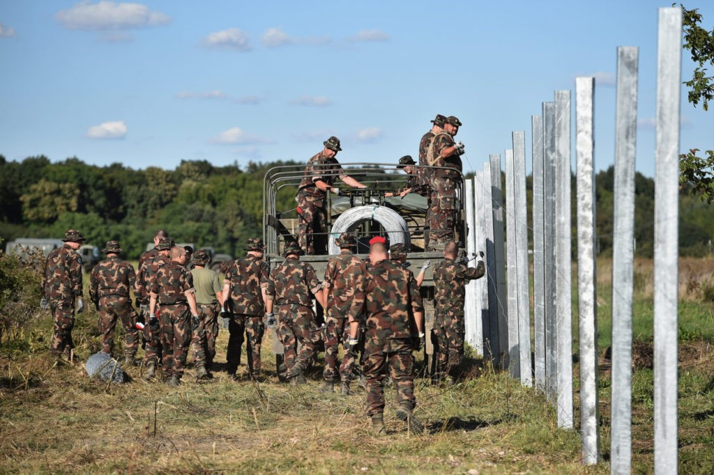 BARANJSKO PETROVO SELO, CROATIA - SEPTEMBER 21: Hungarian soldiers erect a fence at a border point between Croatia and Hungary where migrants are being transported by bus through to Austria on September 21, 2105 in Baranjsko Petrovo Selo,Croatia. Thousands are migrants have being transported by bus and train on to Hungary and Austria as European leaders are set to push for a unified response to the migrant crisis. (Photo by Jeff J Mitchell/Getty Images)