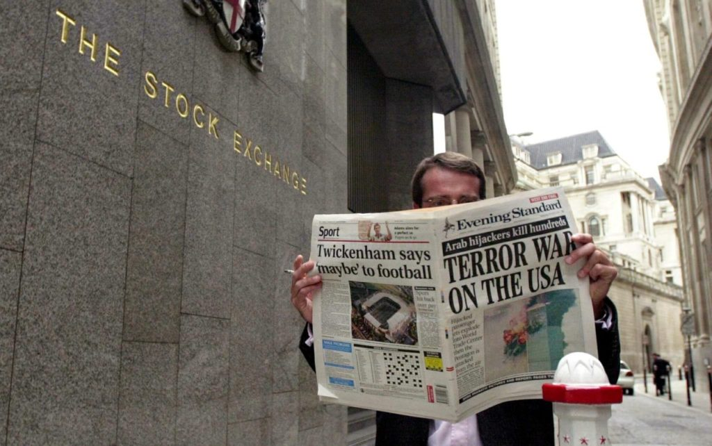 "LONDON, UNITED KINGDOM: A trader of the stock exchange reads the evening paper with"" Terror war on USA"" on the front page 11 September 2001 outside the London stock exchange, following the terrorist attacks at the World Trade Center and the Pentagon in USA earlier today. (Photo credit should read NICOLAS ASFOURI/AFP/Getty Images)"