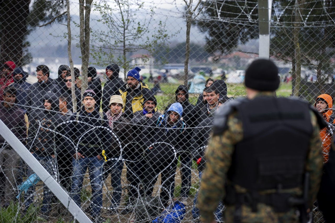 Migrants and refugees stand behind the fence at the Macedonian-Greek border near Gevgelija on March 27, 2016, where thousands of them are stranded by the Balkan border blockade. Dozens of hopeful refugees, some carrying babies, rushed to Greece's overwhelmed Idomeni camp on the sealed border with Macedonia on Sunday following rumours that the frontier would be forced open. The influx came as Greek authorities were trying to evacuate an estimated 11,500 people already stranded at the squalid camp after Balkan states slammed shut their borders, cutting off the migrant route to the European Union. / AFP / Robert ATANASOVSKI (Photo credit should read ROBERT ATANASOVSKI/AFP/Getty Images)