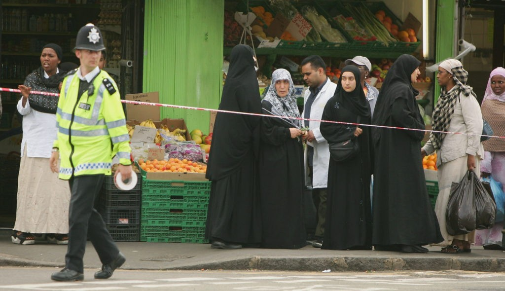 LONDON - JULY 21: Muslim women look on as a British police officer evacuates people from the Shepherd's Bush Tube station area on July 21, 2005 in London, England. Two weeks after the London terrorist bombings on July 7 three London underground train stations have been evacuated following the minor explosions which have hit the capitals transport networks. Warren Street, Oval and Shepherd's Bush have all been targeted aswell as a bomb detonated on a bus in Hackney. (Photo by Scott Barbour/Getty Images)
