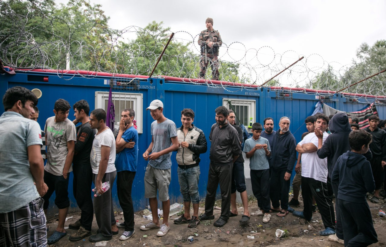 HORGOS, SERBIA - JULY 16: A Hungarian soldier looks down on migrants queueing for food being distributed from a doorway in the border fence close to the E75 Horgas border crossing between Serbia and Hungary on July 16, 2016 in Horgos, Serbia. Serbia has announced that it will start joint army and police patrols on its borders with Bulgaria and Macedonia to curb the illegal entry of migrants and people smuggling. The decision comes days after EU member Hungary began sending back to Serbia all illegal migrants caught within five miles of the border fence that was constructed last year. The new rules have led to hundreds of migrants being stranded along the Serbia-Hungary border. (Photo by Matt Cardy/Getty Images)