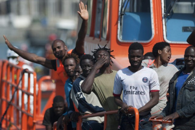 A group of immigrants wave as they arrive on a Spanish coast guard vessel into the southern Spanish port of Malaga on August 31, 2016 after an inflatable boat carrying 52 Africans, nine of them women, was rescued by the Spanish coast guard off the Spanish coast. / AFP / …