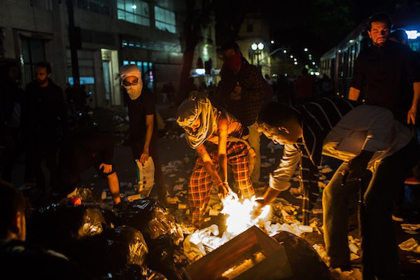 SAO PAULO, BRAZIL - AUGUST 31: Protesters in favor of former Brazil President Dilma Rousseff burn items in the street during a protest march on August 31, 2016 in Sao Paulo, Brazil. Banks and stores were vandalized by protesters after Rousseff was impeached in a 61-to-20 Senate vote earlier in the day. (Photo by Victor Moriyama/Getty Images)