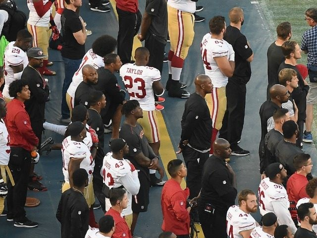 Colin Kaepernick #7 of the San Francisco 49ers takes a knee on the sidelines as military personel hold a flag during the singing of the National Anthem before a preseason game against the San Diego Chargers at Qualcomm Stadium on September 1, 2016 in San Diego, California.