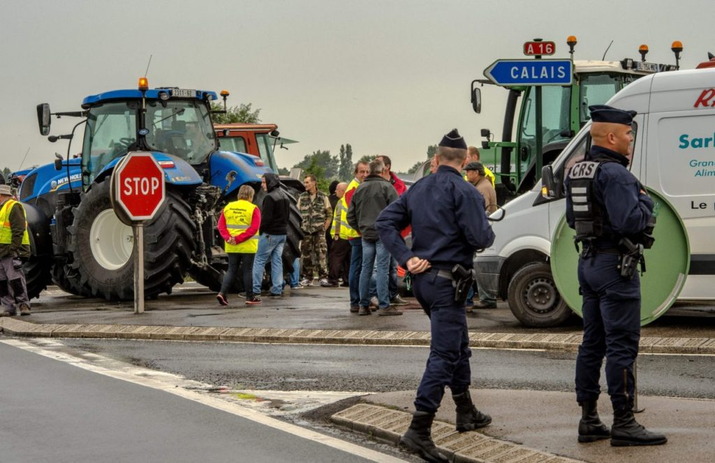 "French police officers stand guard as French farmers gather at Marck prior to meet with a dozen of truck drivers on September 5, 2016 for a slow-down operation on the A16 highway to ask for the dismantling of the so-called ""Jungle"" migrant camp in the French northern port city of Calais. / AFP / PHILIPPE HUGUEN (Photo credit should read PHILIPPE HUGUEN/AFP/Getty Images)"