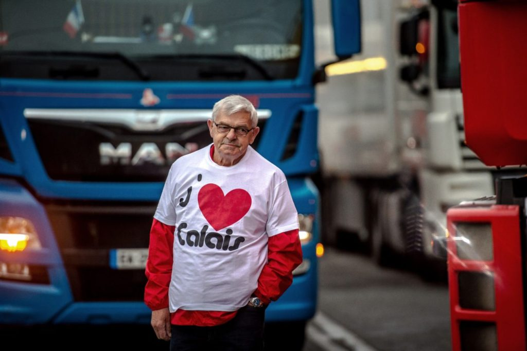 "A man wearing a T-shirt reading ""I love Calais"" stands among trucks as a dozen of truck drivers gather in a parking on September 5, 2016 in Loon Plage prior to a slow-down operation on the A16 highway to ask for the dismantling of the so-called ""Jungle"" migrant camp in the French northern port city of Calais. / AFP / PHILIPPE HUGUEN (Photo credit should read PHILIPPE HUGUEN/AFP/Getty Images)"