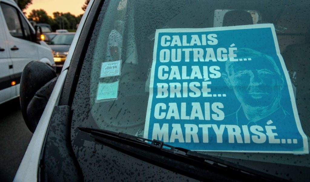 "A picture taken on September 5, 2016 shows a banner reading ""Calais outraged, Calais broken, Calais martyred"" and picturing Charles De Gaulle in a vehicle during a slow-down operation lead by truck drivers on the A16 highway from Loon Plage to Calais to ask for the dismantling of the so-called ""Jungle"" migrant camp in the French northern port city of Calais. / AFP / PHILIPPE HUGUEN (Photo credit should read PHILIPPE HUGUEN/AFP/Getty Images)"