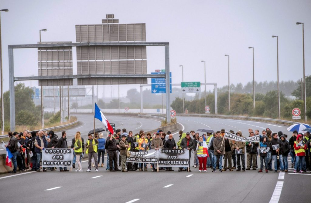 "Residents of the French northern port city of Calais hold French national flags and banners reading ""support to truck drivers"" (L) and ""support to farmers"" (R) as they march on the A16 highway on September 5, 2016 during a ""go-slow"" protest of turk drivers and French Farmers calling for the dismantling of the so-called ""Jungle"" migrant camp in the French northern port city of Calais. French farmers and truckers launched a joint operation on September 5, 2016 to block off main routes in and out of Calais to call for the closure of the sprawling ""Jungle"" migrant camp there. Around 70 trucks began a ""go-slow"" on the main A16 motorway -- the main artery for freight and passengers heading for Britain either via the Channel Tunnel or the Calais port. / AFP / PHILIPPE HUGUEN (Photo credit should read PHILIPPE HUGUEN/AFP/Getty Images)"