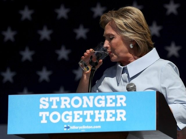 Hillary Clinton pauses to take a drink of water to help soothe a cough during a campaign rally at Luke Easter Park on September 5, 2016 in Cleveland.