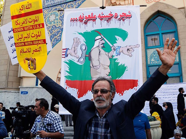 An Iranian man participates in an anti-Saudi demonstration in the capital Tehran on September 9, 2016. With Iranians barred from the annual hajj pilgrimage, thousands protested in Tehran and officials criticised Saudi Arabia's refusal to discuss last year's deadly stampede. The writing on the poster in the background reads in …