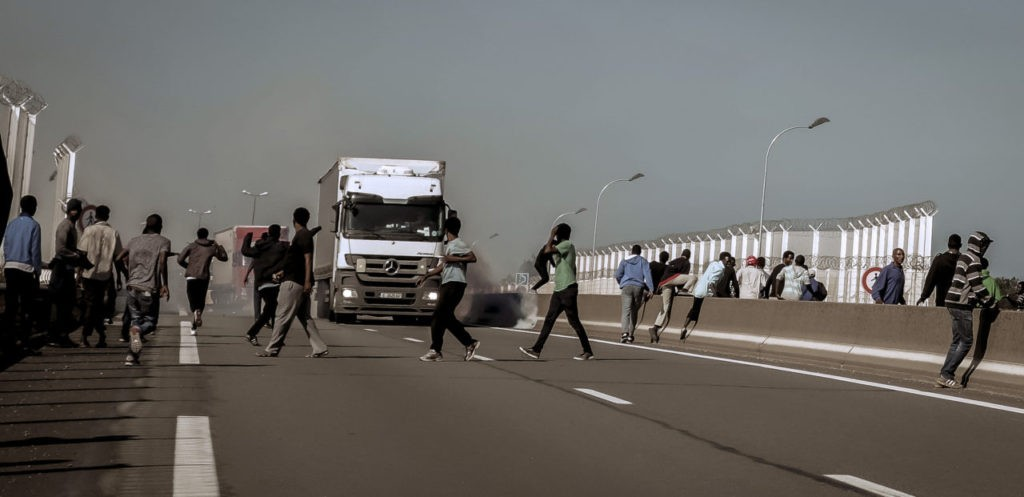 Migrants run away from tear gas during clashes with riot police tryinh to prevent them to get into trucks heading to Great Britain, on September 21, 2016 in Calais. / AFP / PHILIPPE HUGUEN (Photo credit should read PHILIPPE HUGUEN/AFP/Getty Images)
