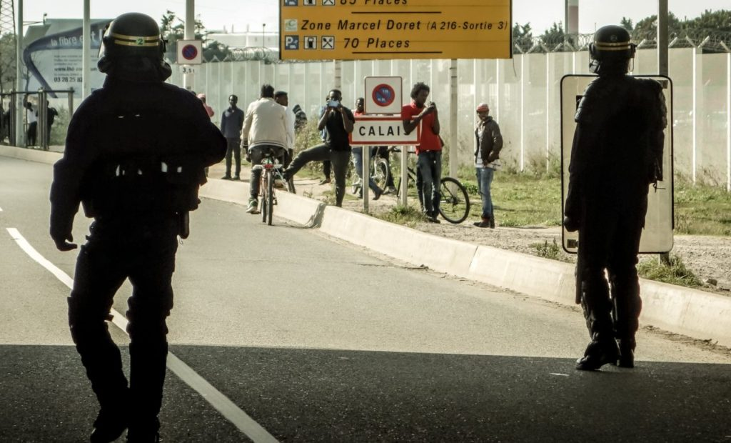 Riot police disperse migrants who were trying to get into trucks heading to Great Britain, on September 21, 2016 in Calais. / AFP / PHILIPPE HUGUEN (Photo credit should read PHILIPPE HUGUEN/AFP/Getty Images)