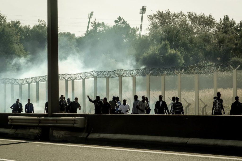 Migrants run away from tear gas during clashes with riot police trying to prevent them from getting into trucks heading to Great Britain, on September 21, 2016 in Calais. / AFP / PHILIPPE HUGUEN (Photo credit should read PHILIPPE HUGUEN/AFP/Getty Images)