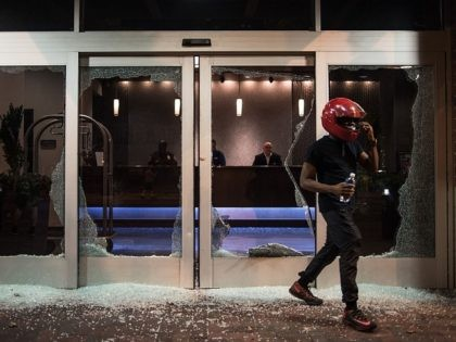 CHARLOTTE, NC - SEPTEMBER 21: A man exits a hotel lobby damaged by protestors September 21, 2016 in downtown Charlotte, NC. Protests in Charlotte began on Tuesday in response to the fatal shooting of 43-year-old Keith Lamont Scott at an apartment complex near UNC Charlotte. (Photo by Sean Rayford/Getty Images)