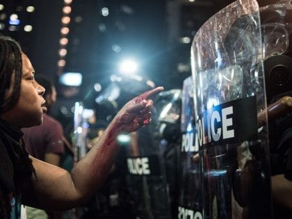 CHARLOTTE, NC - SEPTEMBER 21: With blood covering her hand and arm, a woman points at a police officer on September 21, 2016 in Charlotte, NC. The North Carolina governor has declared a state of emergency in the city of Charlotte after clashes during protests in the city in response …
