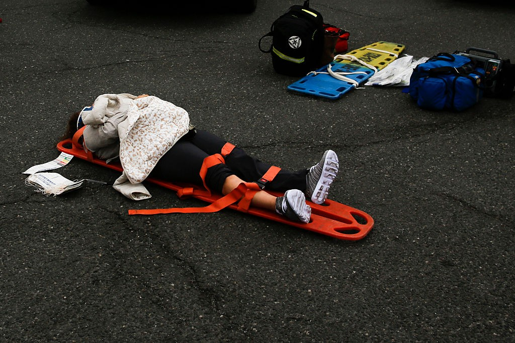 HOBOKEN, NJ - SEPTEMBER 29: A woman waits for treatment of her injuries outside after a New Jersey Transit train crashed into the platform at Hoboken Terminal during morning rush hour September 29, 2016 in Hoboken, New Jersey. According to reports, 3 people have been killed and over 100 injured. (Photo by Eduardo Munoz Alvarez/Getty Images)
