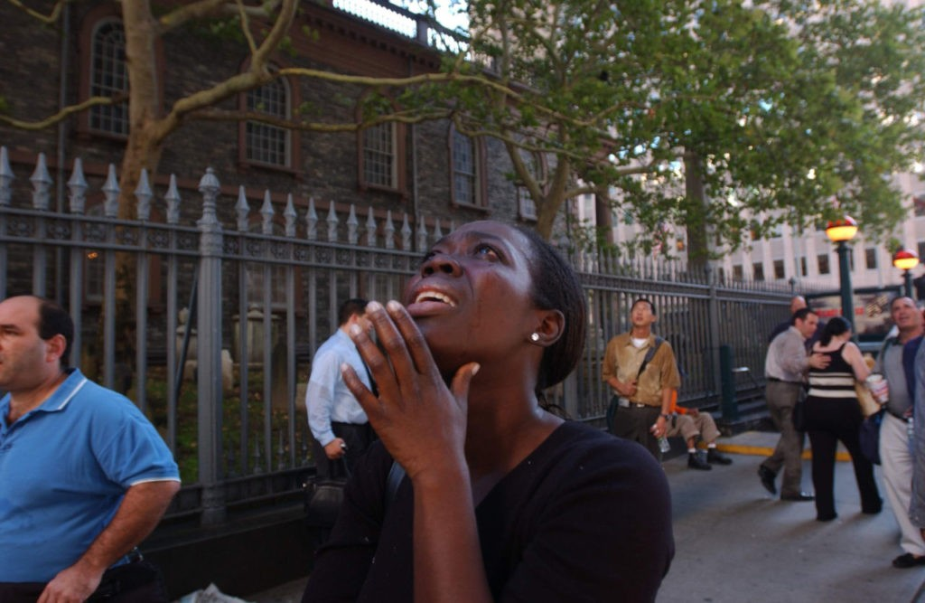 394261 29: A woman reacts in terror as she looks up to see the World Trade Center go up in flames September 11, 2001 in New York City after two airplanes slammed into the twin towers in an alleged terrorist attack. (Photo by Spencer Platt/Getty Images)