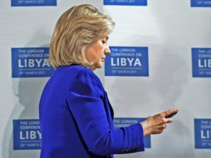 Hillary Clinton checks phone at Libya conference (Stefan Rousseau / Getty)