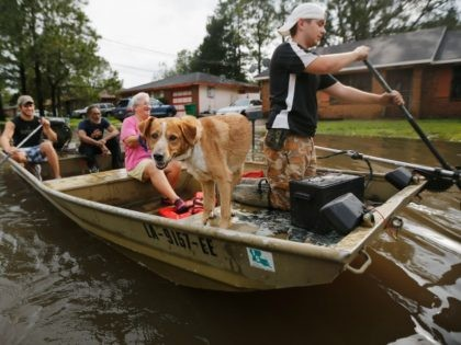 RESERVE, LA - AUGUST 30: Jewel Rico and her dog Chico are rescued from flood waters from Hurricane Isaac on August 30, 2012 in Reserve, Louisiana. Isaac, downgraded Wednesday to a tropical depression, is moving slowly inland, dumping huge amounts of rain and knocking out power to Louisianans in scattered …