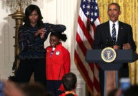 WASHINGTON, DC - SEPTEMBER 29: U.S. first lady Michelle Obama(L) rests her elbow on the head of Olympian Simone Biles (2nd L) as President Barack Obama (R) speaks during an East Room event at the White House September 29, 2016 in Washington, DC. President Obama and the first lady welcome …