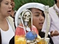 Devotees pray in front of a figure of the Santa Muerte (Holy Death) during a celebration at a sanctuary in Santa Maria Cuautepec, Tultitlan, Mexico on February 7, 2016. Narcos, gangsters and bad guys venerate the Santa Muerte, the Saint of death, probably a syncretism between Middle American and Catholic …