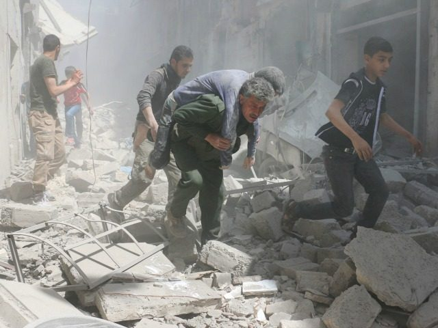 Syrians evacuate an injured man amid the rubble of destroyed buildings following a reported air strike on the rebel-held neighbourhood of Al-Qatarji, in the northern Syrian city of Aleppo, on April 29, 2016. Fresh bombardment shook Syria's second city Aleppo, severely damaging a local clinic as outrage grows over an …