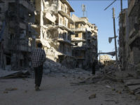 SYRIA, ALEPPO : TOPSHOT - A Syrian man walks past a heavily damaged building following air strikes on rebel-held eastern areas of Aleppo on September 24, 2016. Heavy Syrian and Russian air strikes on rebel-held eastern areas of Aleppo city killed at least 25 civilians on Saturday, the Britain-based Syrian Observatory for Human Rights said, overwhelming doctors and rescue workers. / AFP PHOTO / KARAM AL-MASRI