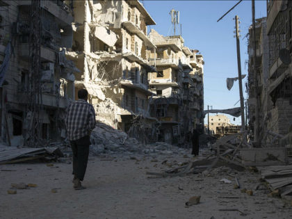 SYRIA, ALEPPO : TOPSHOT - A Syrian man walks past a heavily damaged building following air strikes on rebel-held eastern areas of Aleppo on September 24, 2016. Heavy Syrian and Russian air strikes on rebel-held eastern areas of Aleppo city killed at least 25 civilians on Saturday, the Britain-based Syrian …