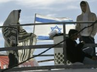The Israeli flag flutters as settlers one in a prayer shawls or Talit bunker down on the roof of one of the nine houses marked for destruction in the Amona settlement in the West Bank, northeast of the town of Ramallah, 31 January 2006.