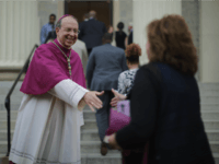 BALTIMORE, MD - APRIL 25: Catholic Archbishop of Baltimore William Lori (L) welcomes people to the Basilica of the National Shrine of the Assumption of the Blessed Virgin Mary for an interfaith prayer service for peace marking the first anniversary of unrest following the death of Freddie Gray April 25, …