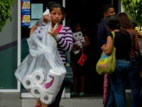 A woman leaves after buying toilet paper at a supermarket of Petare neighborhood in Caracas, on June 13, 2016. Facing mounting pressure from food shortages, looting and increasingly violent protests, Venezuelan authorities on Friday announced the next stage of a recall referendum against embattled President Nicolas Maduro. / AFP / …