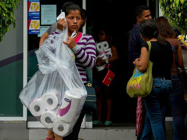 A woman leaves after buying toilet paper at a supermarket of Petare neighborhood in Caracas, on June 13, 2016. Facing mounting pressure from food shortages, looting and increasingly violent protests, Venezuelan authorities on Friday announced the next stage of a recall referendum against embattled President Nicolas Maduro. / AFP / FEDERICO PARRA (Photo credit should read FEDERICO PARRA/AFP/Getty Images)