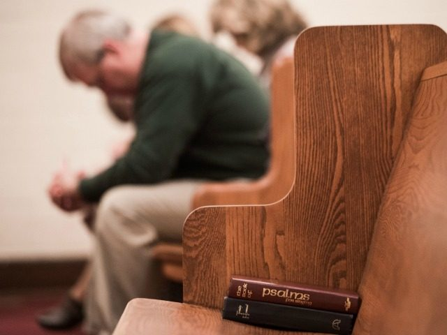 People bow their heads in prayer during a Sunday evening service at Grace Orthodox Presbyterian Church in Lynchburg, Virginia, on January 17, 2016. The young evangelical Christians at Liberty University in Virginia are facing a dilemma this election season: whether to follow in the footsteps of their parents and back …