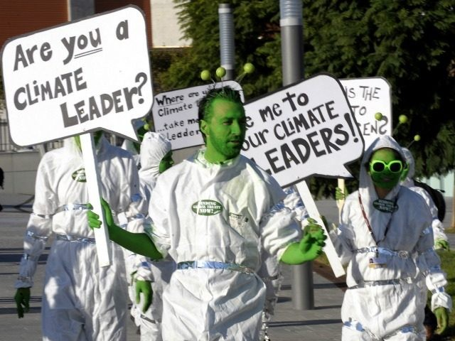 Activists of the environmental group Avaaz perform wearing costumes representing an alien delegation mingled with UN delegates holding placards reading 'Where is your climate leader ? Take me your climate leader' during the Barcelona Climate Change Talks on November 6, 2009 in Barcelona. Some 180 countries hold the last day of climate talks during the before December's Copenhagen conference tasked with tackling the threat of global warming AFP PHOTO / LLUIS GENE (Photo credit should read LLUIS GENE/AFP/Getty Images)