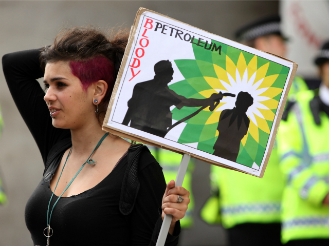 LONDON, ENGLAND - SEPTEMBER 01: A climate change protester holds an anti-BP banner in front of Shell petroleum's headquarters on September 1, 2009 in London, England. Climate campaigners have also been staging a week long protest camp in Blackheath south London. (Photo by Oli Scarff/Getty Images)