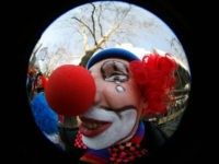 A carnival reveller dressed as a clown celebrates on the street in Berlin February 18, 2007. Clowns from around the world are falling over their very large shoes to protest the publication of a British study which reported that children don't like them. REUTERS/Pawel Kopczynski