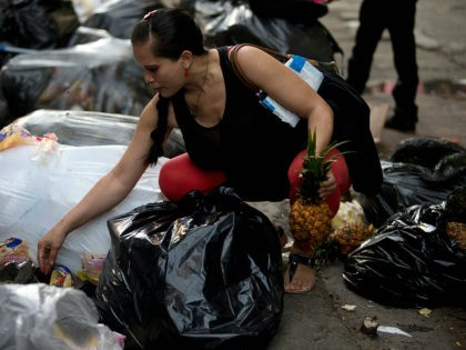 This June 2, 2016 photo shows a pregnant woman who did not want to be named, holding a pineapple in one hand as she continues to pick through garbage bags outside a supermarket in downtown Caracas, Venezuela. Unemployed people converge every dusk at the trash heap to pick through rotten …