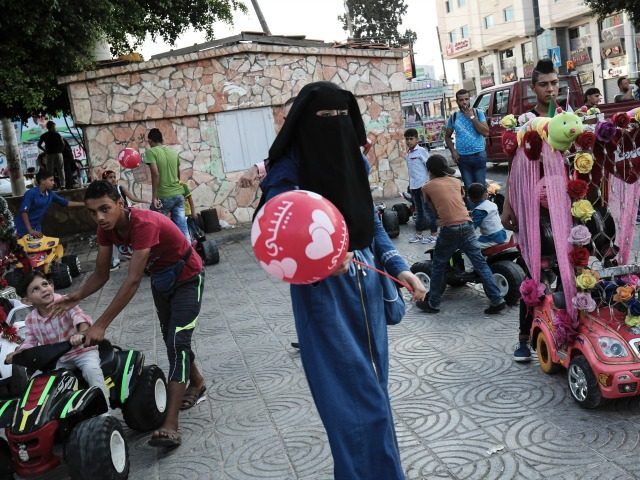 A Palestinian woman holds a balloon in the street in Gaza City as Muslims celebrate the second day of Eid al-Adha (Festival of Sacrifice) holiday on September 13, 2016. / AFP / SAID KHATIB (Photo credit should read SAID KHATIB/AFP/Getty Images)