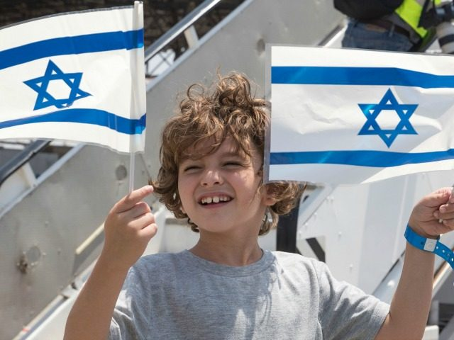Newly arrived Jewish immigrants coming from France hold Israeli flags as they step off the plane upon their arrival at the Ben Gurion International Airport near Tel Aviv on July 20, 2016. More than 200 French Jews were expected to immigrate to Israel aboard this aliyah (Immigration to Israel) flight, …