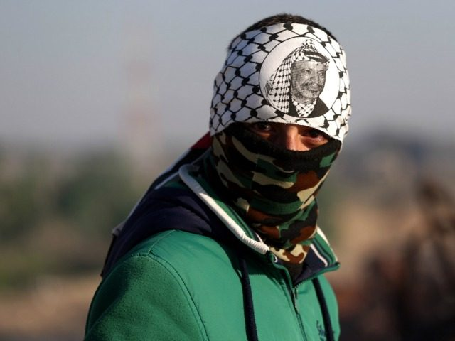 A Palestinian protester, wearing a traditional keffiyeh and bearing the portrait of late Palestinian leader Yasser Arafat, looks on during clashes Israeli soldiers near the border between Israeli and the eastern outskirts of Gaza City on November 13, 2015. AFP PHOTO / MOHAMMED ABED (Photo credit should read MOHAMMED ABED/AFP/Getty …