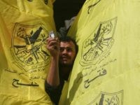 A Palestinian supporter of the secular Fatah movement takes a picture with his mobile phone through his party's flags during a huge gathering in Gaza city, 12 November 2007, to mark the anniversary of the death of Yasser Arafat. Hamas police killed six people in Gaza City today as hundreds …