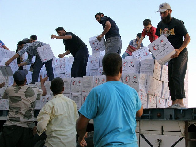 Syrians unload boxes after a 48-truck convoy from the ICRC, SARC and UN entered the Syrian rebel-held town of Talbiseh, a besieged area in northern rural Homs, on July 26, 2016. The convoy, the second biggest convoy ever in Syria, carried food aid for 40,000 people and bulk food to support collective kitchens operating in the area, hygiene kits, mattresses, blankets and the kitchen sets. Since 2012, the town of Talbisseh has been besieged and heavily affected by ongoing fighting. / AFP / MAHMOUD TAHA (Photo credit should read MAHMOUD TAHA/AFP/Getty Images)