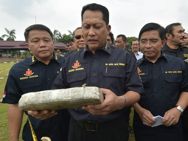 INDONESIA, JAKARTA : Budi Waseso (C), Indonesian chief of criminal investigation division, holds a seized marijuana block at the national police headquarters in Jakarta on May 11, 2015. Indonesian police revealed 2.1 tons of marijuana packages as evidence from recent raids. AFP PHOTO / ADEK BERRY2015.
