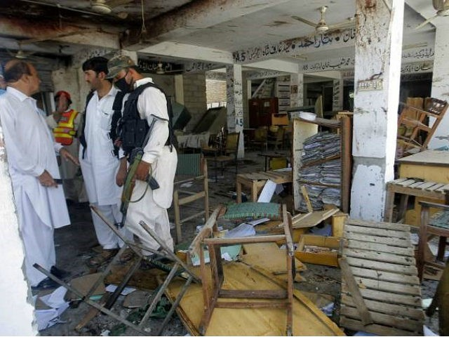 Pakistani officials examine a site of a bombing in Mardan, Pakistan, Friday, Sept. 2, 2016. Northwestern Pakistan was struck by two separate militant attacks on Friday, when gunmen wearing suicide vests stormed a Christian colony near the town of Peshawar, killing one civilian, and a suicide bomb attack on a district court in the town of Mardan. (AP Photo/Mohammad Sajjad)