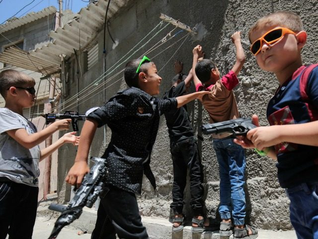 Palestinian children play with toy guns in the southern Gaza Strip town of Rafah on July 7, 2016, on the second day of Eid al-Fitr holiday, which marks the end of the holy Muslim month of Ramadan. / AFP / SAID KHATIB (Photo credit should read SAID KHATIB/AFP/Getty Images)