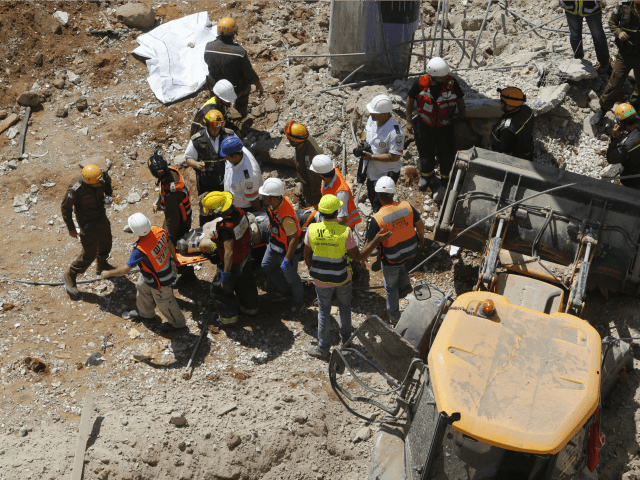 Israeli medics and emergency units carry a wounded person away on a stretcher from a construction site after an underground car park collapsed on September 5, 2016 in the Ramat Hahayal neighbourhood in the coastal city of Tel Aviv. Police reported 18 wounded, including one seriously, one moderately and 16 …