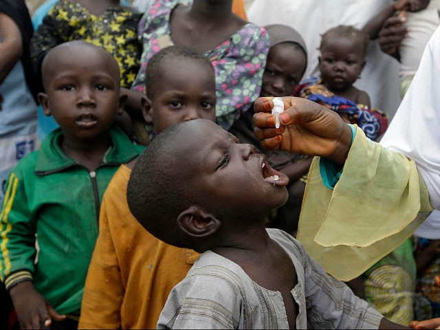 In this photo taken on Sunday, Aug. 28, 2016, a health official administers a polio vaccine to children at a camp for people displaced by Islamist Extremist in Maiduguri, Nigeria. An emergency polio vaccination campaign aimed at reaching 25 million children this year has begun in parts of Nigeria newly freed from Boko Haram Islamic extremists, with fears that many more cases of the crippling disease are likely to be found. (AP Photo/Sunday Alamba)